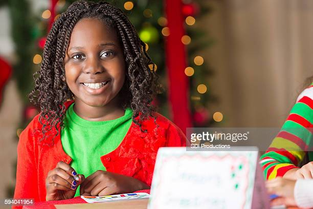 Smiling young girl making Christmas cards