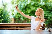 Smiling young girl making selfie photo on smartphone in city cafe