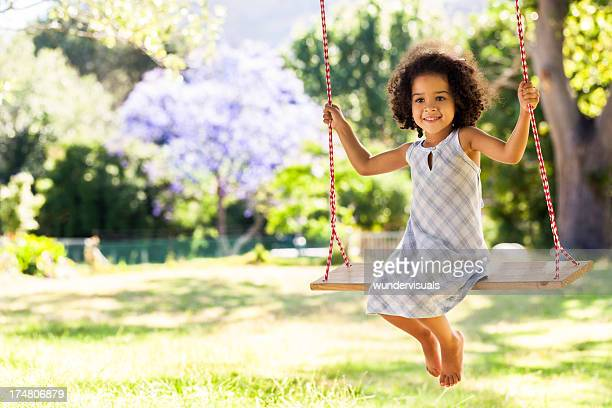 Smiling young girl on a swing in a park