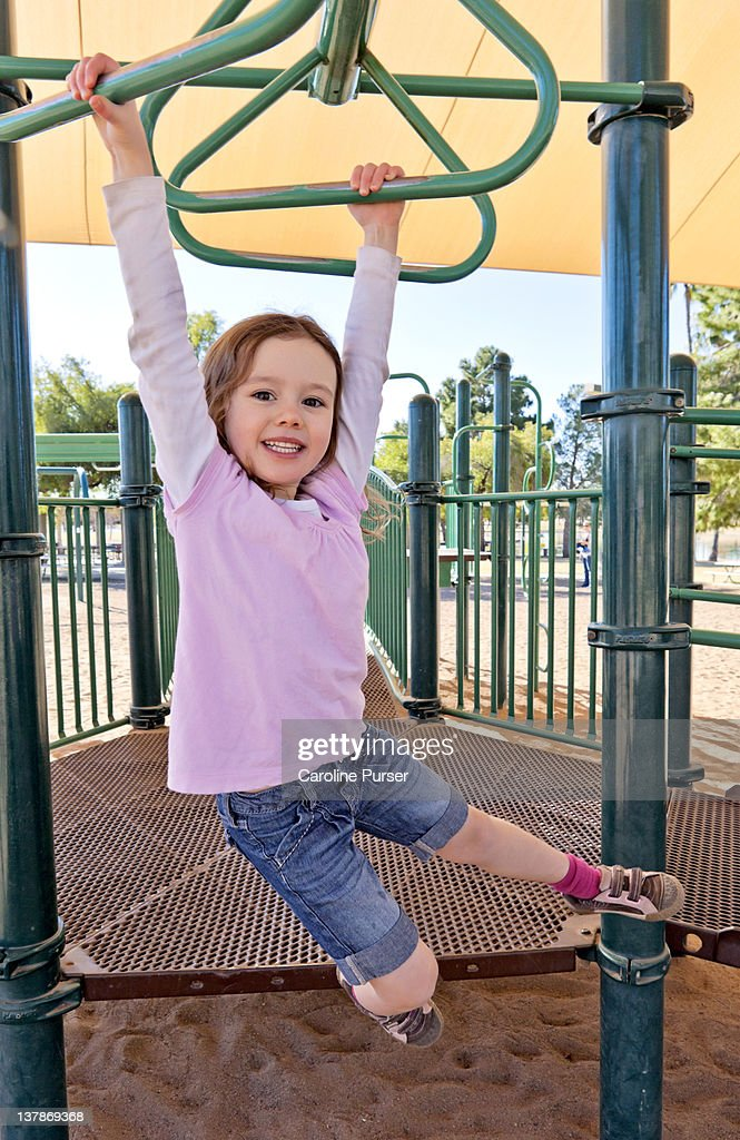 Smiling young girl on monkey bars