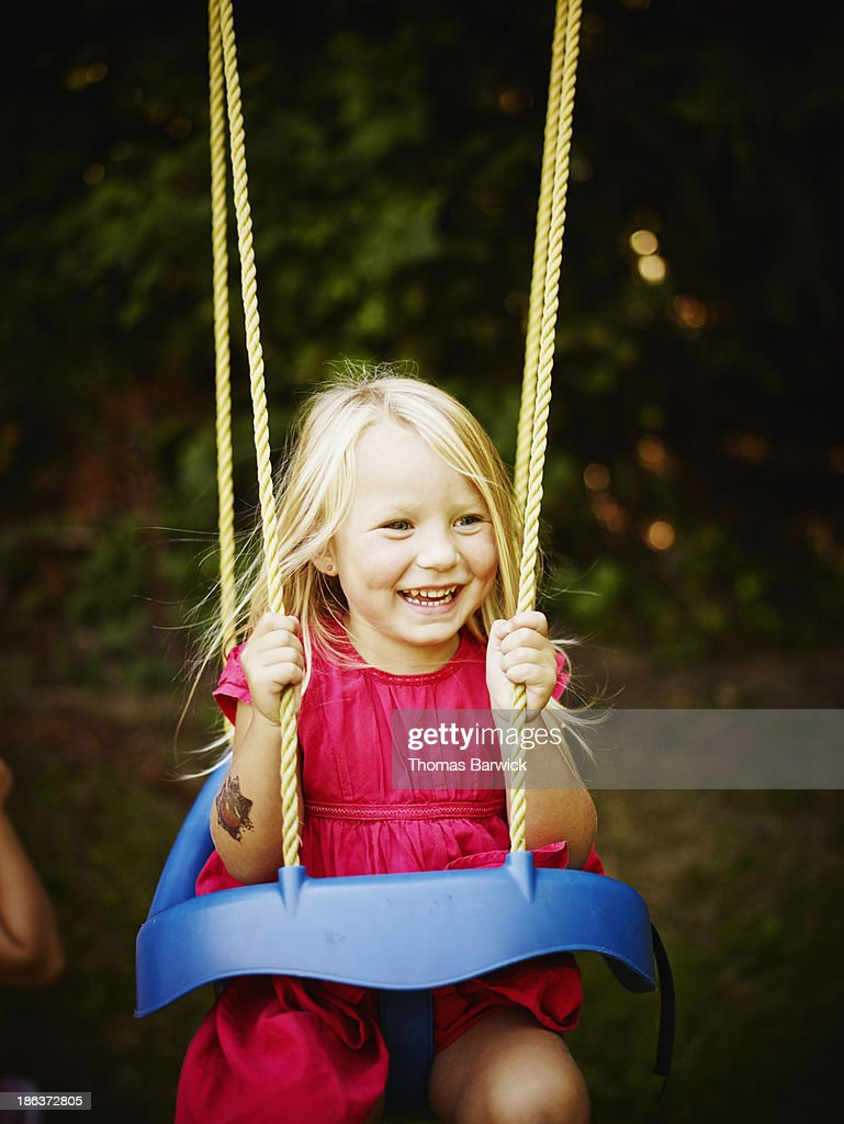 smiling young riding on swing in backyard stock photo getty