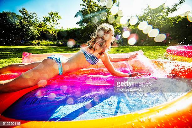 Smiling young girl splashing into pool