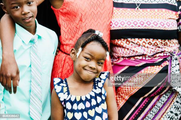 Smiling young girl standing with siblings for family portrait