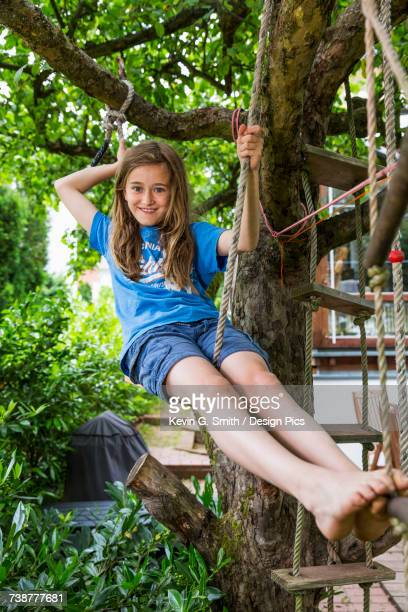 A smiling young girl wearing a blue t-shirt, sitting outside on a rope ladder in a tree