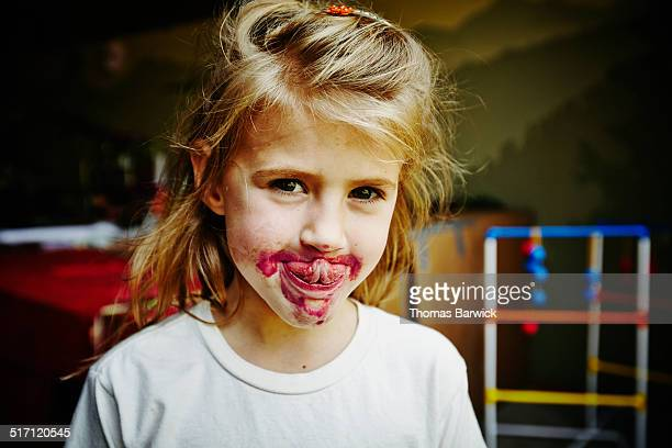 Smiling young girl with face covered in popsicle