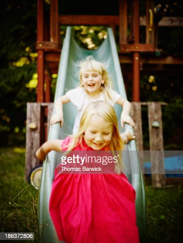 Smiling young girls riding down slide laughing : Foto de stock