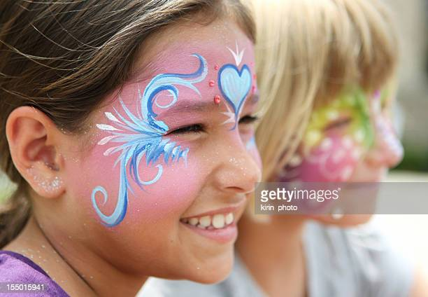 Smiling young girls wearing colorful face paint