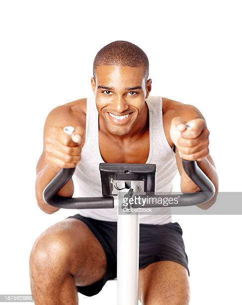 Smiling young guy spinning on a fitness bike