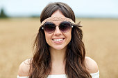 nature, summer, youth culture and people concept - smiling young hippie woman in sunglasses outdoors