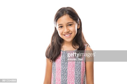 Smiling young hispanic girl posing and looking at the camera over white background : Stock Photo