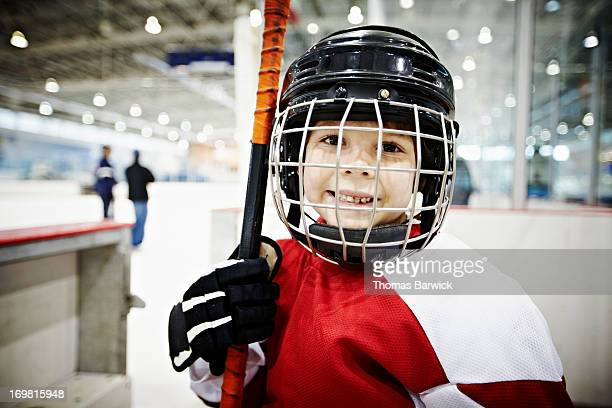 Smiling young hockey player in players box