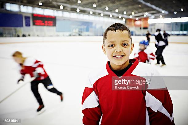 Smiling young hockey player standing on ice