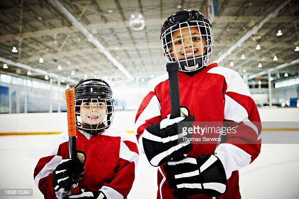 Smiling young hockey players standing on ice