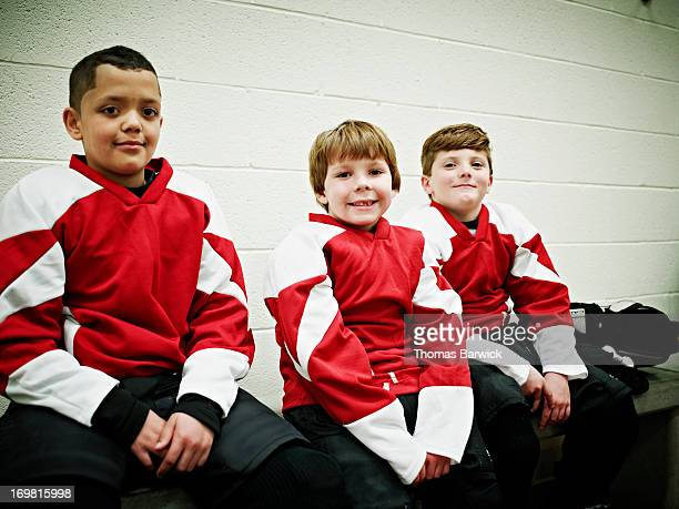 Smiling young ice hockey players in locker room
