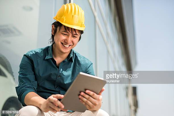 Smiling young Japanese architect reading something on touchpad outdoors.