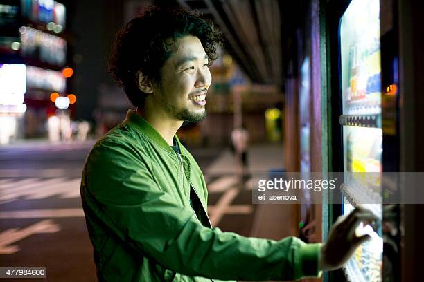 Smiling Young Japanese Man Using Vending Mashine in Tokyo.