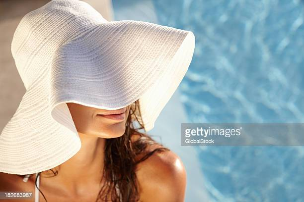 Smiling young lady relaxing by swimming pool