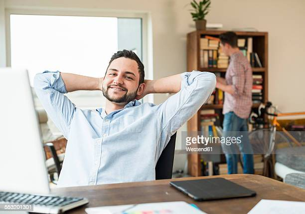 Smiling young man at desk leaning back