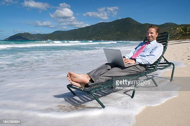 Smiling Young Man Businessman Relaxing on Beach Chair with Laptop