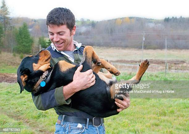 Smiling young man craddling large Rottweiler puppy