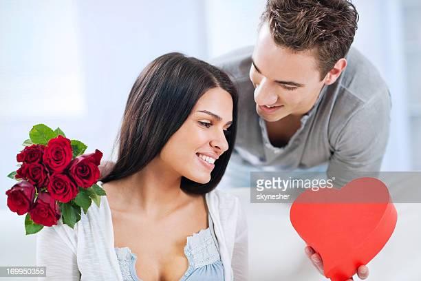 Lächelnder, junger Mann geben einen Blumenstrauß für seine Freundin mit Rosen