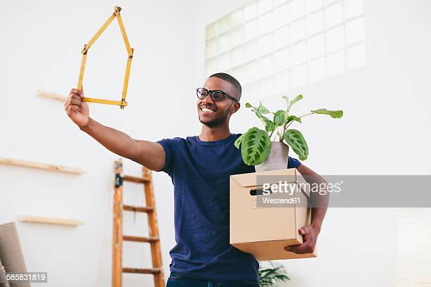 Smiling young man holding cardboard box and pocket rule shaped like a house