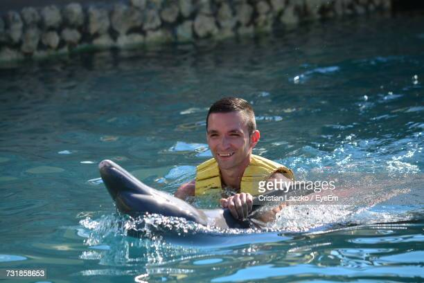 Smiling Young Man Holding Dolphin In Sea