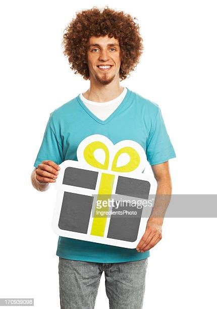 Smiling young man holding gift sign isolated on white background.