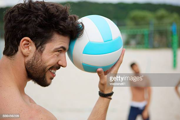 Smiling young man holding volleyball