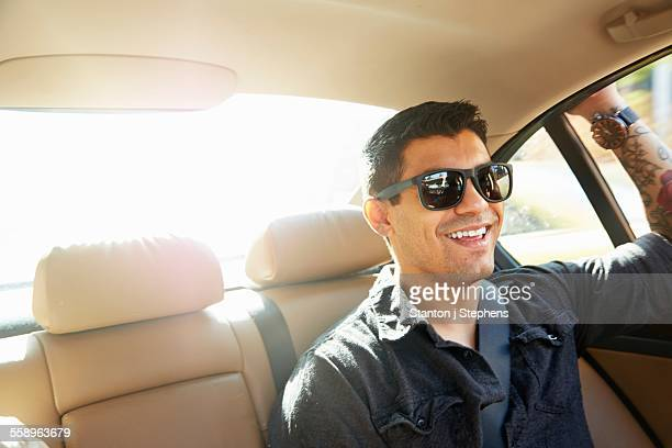 Smiling young man in back seat of car