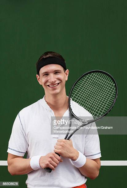 smiling young man in tennis outfit holding racket