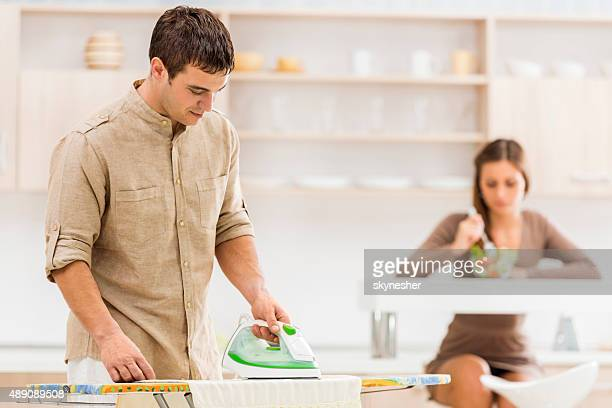 Smiling young man ironing clothes at home.