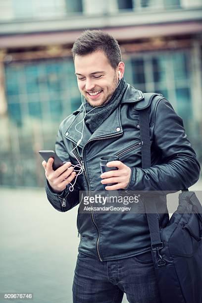 笑う若い男性の音楽を聴きながら、コーヒーを飲みながら屋外