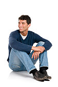 Smiling young man looking away with embarassement isolated on white background.