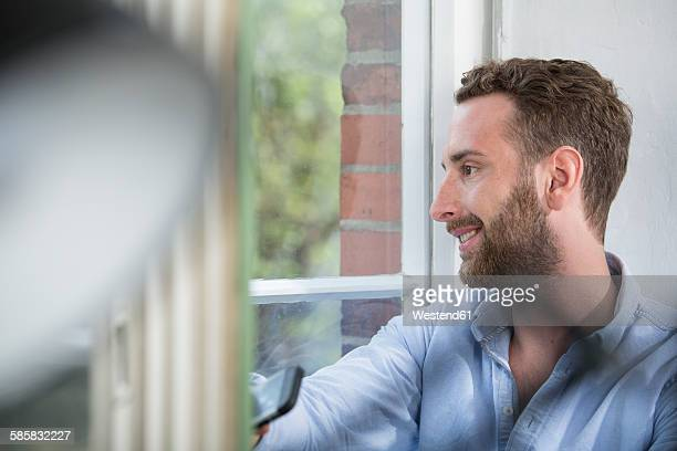 Smiling young man looking out of the window