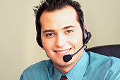 Smiling young man on headset in office