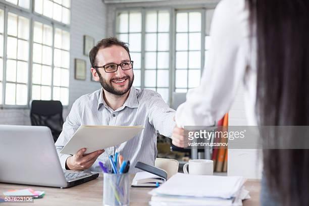 Souriant jeune homme reçoit les documents sur le bureau