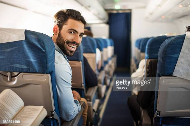 Smiling young man traveling by plane.