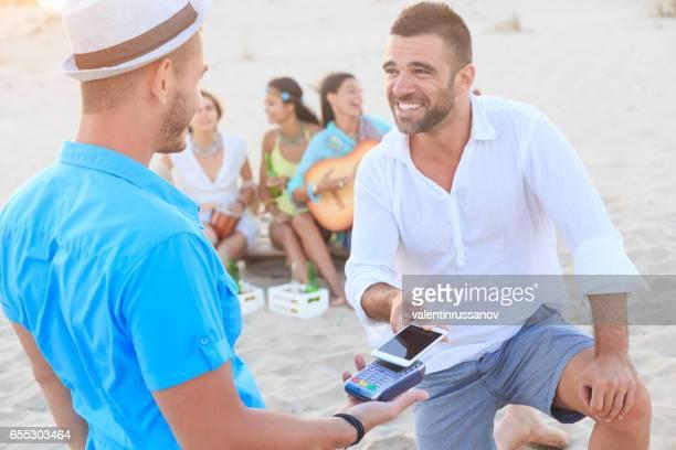 Sonriente a joven usando tarjeta de crédito para el pago sin contacto en la playa