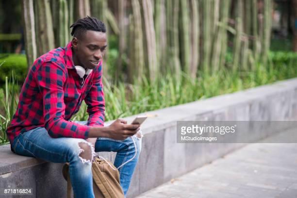 Leende ung man med hjälp av mobiltelefon.