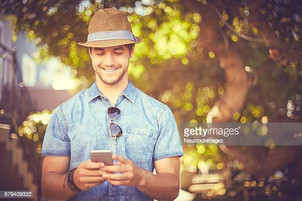 Smiling young man using smart phone on street