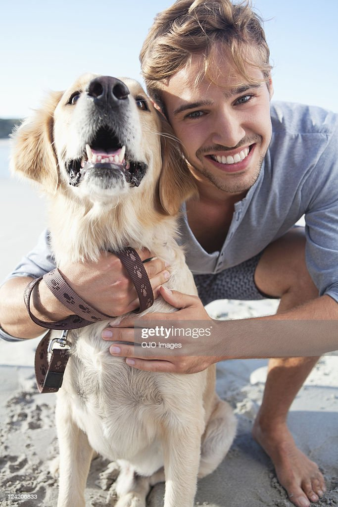 Smiling young man with dog at the beach : Stock Photo