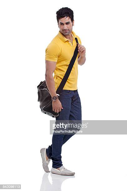 Smiling young man with duffel bag over white background