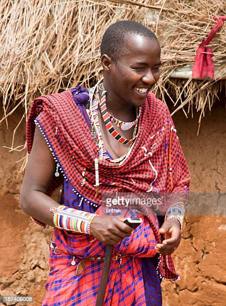 Smiling young Masai with mobile outside his dung hut Kenya