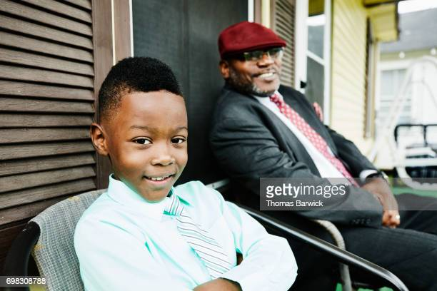 Smiling young nephew sitting with uncle on front porch of home