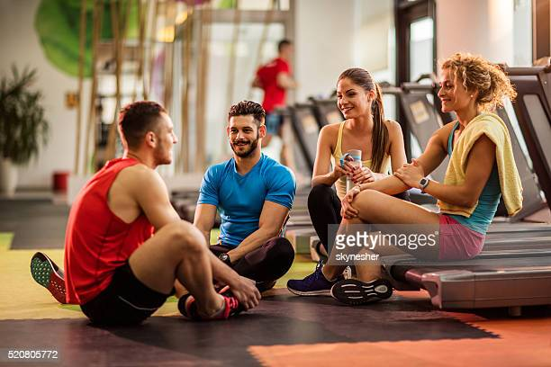 Smiling young people relaxing in a gym and communicating.