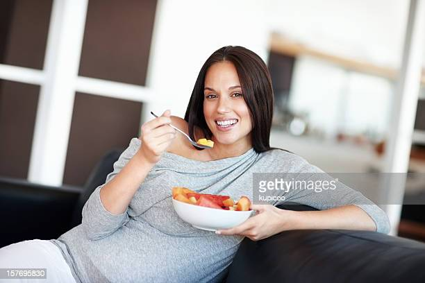 Smiling, young pregnant woman eating fruit salad on couch