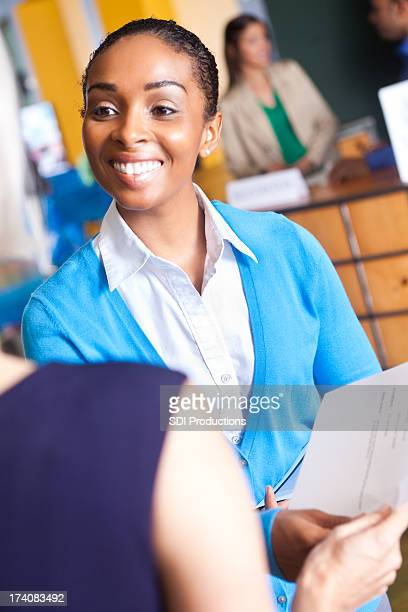 Smiling young professional businesswoman presenting resume at job fair