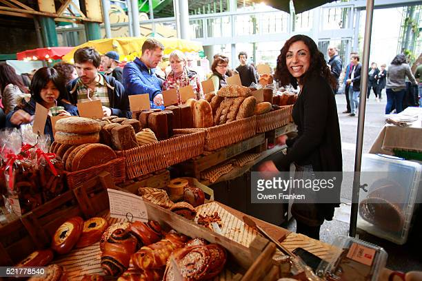 smiling young saleswoman at a bread stand in Borough Market, London