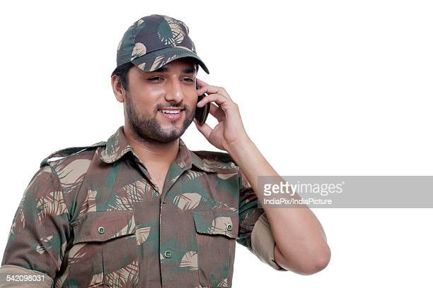 Smiling young soldier talking on cell phone